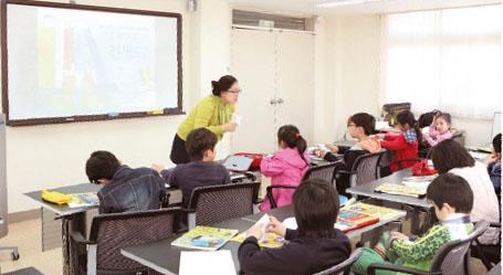이번 수업을 진행한 염지현 기자가 학생들에게 A4용지를 이용한 삼각기둥 만들기를 설명하고 있다.