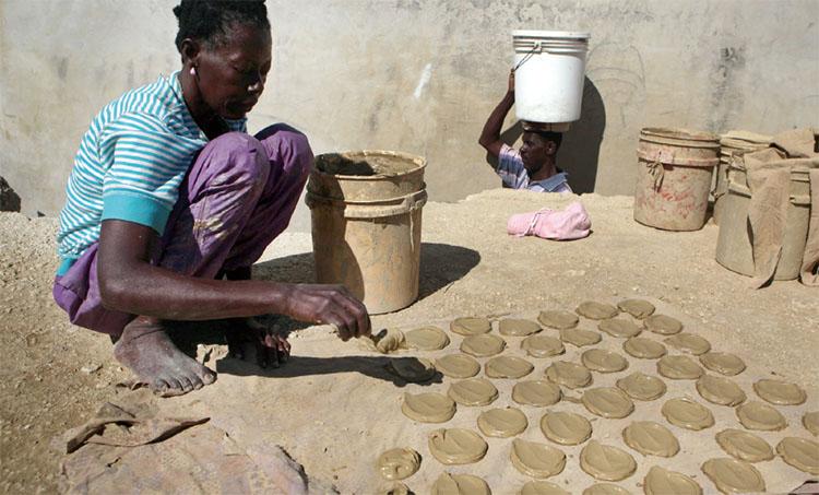 아이티의 한 여성이 점토에 마가린과 소금을 첨가한 반죽을 햇빛 아래에 건조시키고 있다. 굶주린 배를 채우기 위해 먹는다고 알려졌지만, 실제로는 임산부들이 약용으로 많이 먹는다.