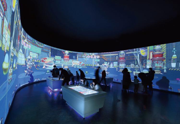 테마관 내 프로시온(인터랙티브 월)의 모습. 관람객들이 외계인을 직접 만들어 대형 영상에 띄우고 있다.